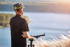 Portret młoda cyklista pozycja na wzgórzu nad rzeka przeciw niebieskiemu niebu z chmurami Fotografia Stock