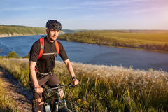 Portret młoda cyklista pozycja na wzgórzu nad rzeka przeciw niebieskiemu niebu z chmurami Obrazy Stock