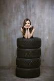 Portret młoda dziewczyna która jest inside samochodów oponami na, Zdjęcia Royalty Free