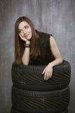Portret młoda dziewczyna która jest inside samochodów oponami na, Obraz Royalty Free