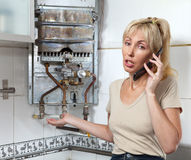 Portret młoda kobieta gospodyni domowa dzwoni w warsztacie na naprawie benzynowi wodni nagrzewacze Zdjęcia Stock