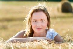 Portret młoda kobieta która opiera na beli siano Zdjęcia Royalty Free