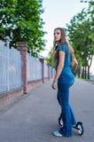 Portret m?oda nastolatek brunetki dziewczyna z d?ugie w?osy nap?dow? hulajnog? na miasto ulicie fotografia royalty free