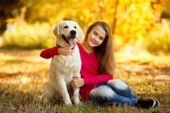 Portret młodej dziewczyny obsiadanie na ziemi z jej psim aporterem w jesieni scenie Obrazy Stock