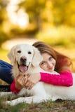 Portret młodej dziewczyny obsiadanie na ziemi z jej psim aporterem w jesieni scenie Zdjęcie Stock