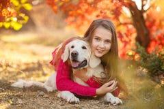 Portret młodej dziewczyny obsiadanie na ziemi z jej psim aporterem w jesieni scenie Fotografia Royalty Free