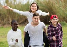 Portret młodzi przyjaciele biega na polu Zdjęcia Stock