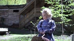 Portret mała ładna dziewczyny pozycja przed starym wiejskim drewnianym domem trzyma staromodną łozinową koszałkę wewnątrz zbiory