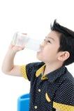 Portret Mała azjatykcia chłopiec pije szkło mleko obrazy stock