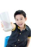 Portret Mała azjatykcia chłopiec pije szkło mleko fotografia royalty free
