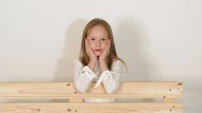 Portret mała dziewczynka blisko ławki w studiu z białym tłem zbiory
