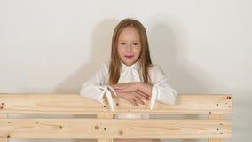 Portret mała dziewczynka blisko ławki w studiu z białym tłem zbiory wideo