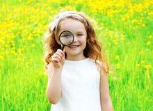 Portret mała dziewczynka patrzeje przez powiększać - szklany lato Zdjęcia Royalty Free