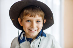 Portret mała szkolna dzieciak chłopiec jest ubranym kowbojskiego kapelusz Fotografia Stock