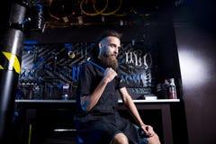 Portret małego biznesu właściciel młody człowiek z brodą Faceta rowerowego mechanika pracownika warsztatowy obsiadanie z narzędzi zdjęcie stock
