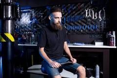 Portret małego biznesu właściciel młody człowiek z brodą Faceta rowerowego mechanika pracownika warsztatowy obsiadanie z narzędzi zdjęcia royalty free