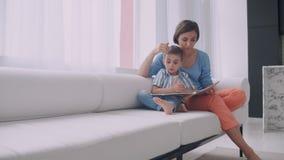 Portret małej ślicznej chłopiec czytelnicza książka z matką podczas gdy siedzący na skrytce zdjęcie wideo