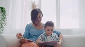 Portret małej ślicznej chłopiec czytelnicza książka z matką podczas gdy siedzący na skrytce zbiory wideo