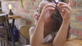 Portret małej dziewczynki łasowania cukierki tort i ono uśmiecha się przy stołem w kawiarni Stawia czoło ślicznej dziewczyny uśmi zdjęcie wideo