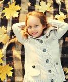 Portret małej dziewczynki dziecka szczęśliwy uśmiechnięty lying on the beach ma zabawę z żółtymi klonowymi liśćmi w pogodnym jesi Fotografia Stock