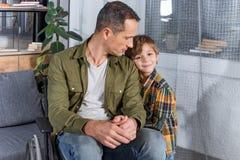 portret mały syn i ojciec w wózku inwalidzkim obraz royalty free