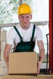 Portret magazynowy pracownik podnosi pudełko Fotografia Royalty Free