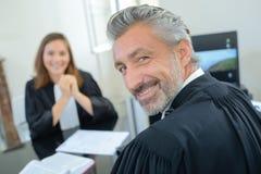 Portret mannelijke en vrouwelijke advocaten in robes royalty-vrije stock afbeeldingen