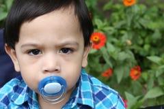 Portret markotna chłopiec na tle kwiaty z dziecko atrapą zdjęcia royalty free