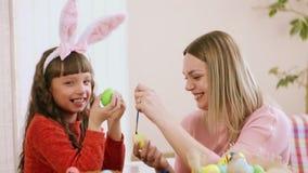 Portret matka i córka który malują Easter jajka Dziewczyn spojrzenia uważnie przy kamerą i biorą ona oczy daleko od zbiory