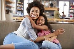 Portret matki I córki obsiadanie Na kanapy Śmiać się zdjęcia stock
