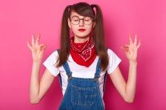 Portret medytować atrakcyjnej dziewczyny z długie włosy, jest ubranym t koszula, drelichowych kombinezony i bandany na szyi, M zdjęcie stock