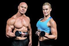 Portret mięśniowi mężczyzna i kobiety podnośni dumbbells Fotografia Royalty Free