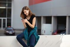 Portret miastowa modna dziewczyna używa mądrze telefon outdoors w mieście Zdjęcie Stock
