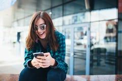 Portret miastowa modna dziewczyna używa mądrze telefon outdoors w mieście Zdjęcia Stock