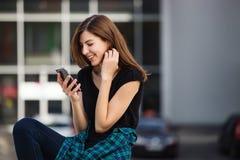 Portret miastowa modna dziewczyna używa mądrze telefon outdoors w mieście Obrazy Royalty Free