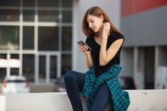 Portret miastowa modna dziewczyna używa mądrze telefon outdoors w mieście Obraz Stock