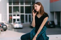 Portret miastowa modna dziewczyna używa mądrze telefon outdoors w mieście Fotografia Stock