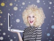 Portret śmieszna dziewczyna w blondynki peruce z laptopem. Obrazy Royalty Free