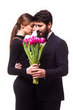 Portret młoda rodzinna para w miłości z bukietem lila tulipany odziewa na białym backround pozować ubierał w klasyku Obrazy Royalty Free