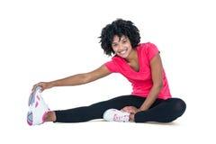 Portret młodej kobiety macania palec u nogi podczas gdy ćwiczący Obrazy Royalty Free