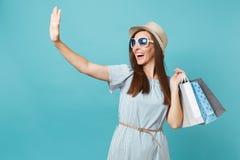 Portret modna atrakcyjna szczęśliwa kobieta w lato sukni, słomiany kapelusz, okulary przeciwsłoneczni trzyma pakunki zdojest z za zdjęcia stock