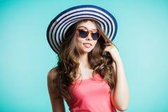 Portret modna dziewczyna z kapeluszem na jego głowie nad błękitnym tłem Dziewczyna ono uśmiecha się pięknie i spojrzenia przy kam zdjęcia royalty free