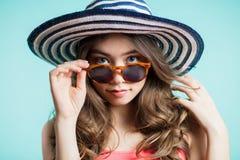 Portret modna dziewczyna z kapeluszem na jego głowie nad błękitnym tłem Dziewczyna ono uśmiecha się pięknie i spojrzenia przy kam fotografia stock