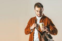 portret modny mężczyzna patrzeje rozporządzalnego filiżanka kawy w ręce z torbą obraz royalty free