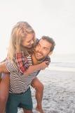 Portret młody człowiek piggybacking pięknej kobiety Zdjęcia Stock