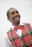 Portret młody człowiek w szkockiej kraty kamizelce i czerwień łęku krawacie, studio strzał Zdjęcia Royalty Free