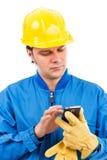Portret młody pracownik budowlany używa telefon komórkowy Zdjęcie Royalty Free