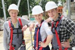 Portret młodzi ludzie z hełmami w budowie Zdjęcia Royalty Free