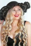 Portret Mooi jong vrouwenblonde in een zwarte kleding en een hoed met een halslijn, prachtig glimlachend, rode lippenstift royalty-vrije stock afbeelding