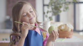 Portret mooi meisje die met schitterend haar in blauwe schort paasei met een kleine borstelzitting schilderen in stock videobeelden